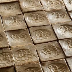 Les étapes de fabrication du savon d'Alep !🌿Cette fabrication se déroule de novembre à mars, période pendant laquelle les hommes travaillent au-dessus d'un grand chaudron de 10 000 litres chauffé à 120 degrés, rempli de 5 tonnes d'huile d'olive, 6 tonnes d'eau et 500 kilos de soude, mélange indispensable à la saponification. 🌿Une pâte verte, épaisse, se forme au rythme de l'ébullition. 🌿Une fois l'huile de baie de laurier ajoutée et la cuisson terminée, la pâte est coulée à même le sol et se glace en seulement quelques heures. Les savons sont ensuite découpés grâce à un râteau tiré en attelage et frappés à la main, sur leur face supérieure, d'une marque en bois ou en laiton. 🌿Enfin, le savon sèche durant neuf mois pour révéler son aspect définitif : plus foncé et plus dur à l'extérieur, plus vert et moelleux à l'intérieur.#tadepaysdulevant #savondalep #fabricationsavondalep #madeinsyria #fabriqueensyrie #alepposoap #veritablesavondalep